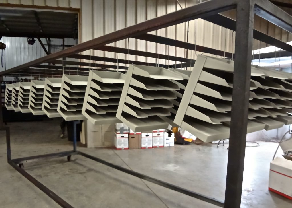 A large order of steel trays cooling after powder coating