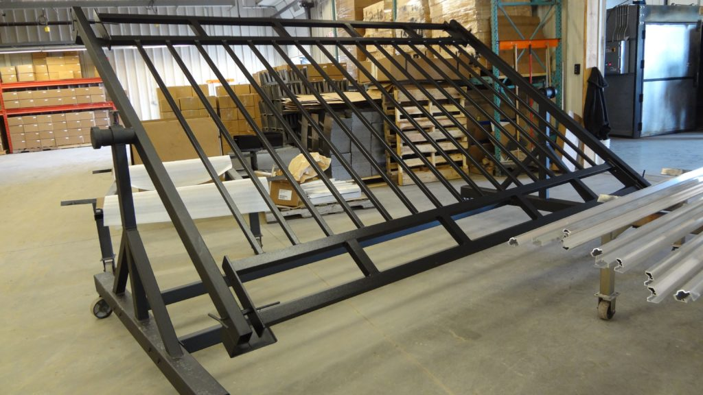 A steel fence railing cools after being coated in black