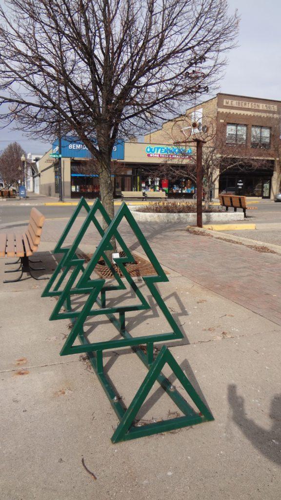 Tree-shaped bike rack with a green powder coat in downtown Bemidji