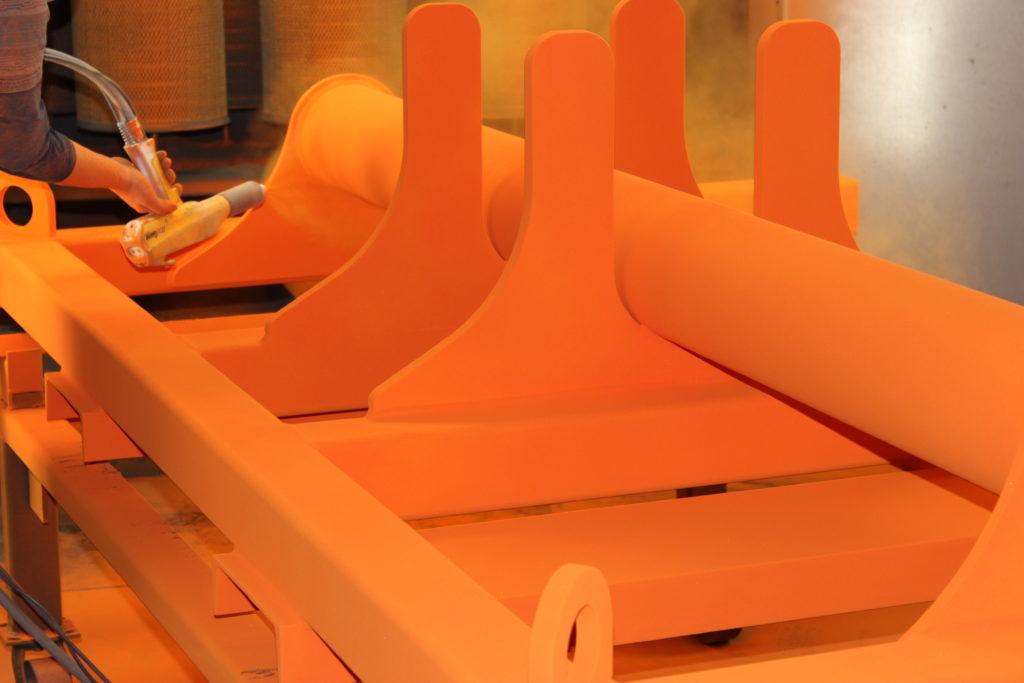 Large industrial equipment undergoing a safety orange powder coating