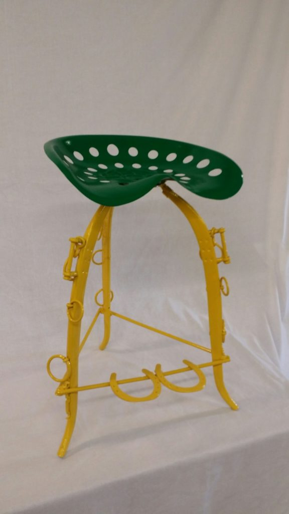Tractor seat coated in green and yellow